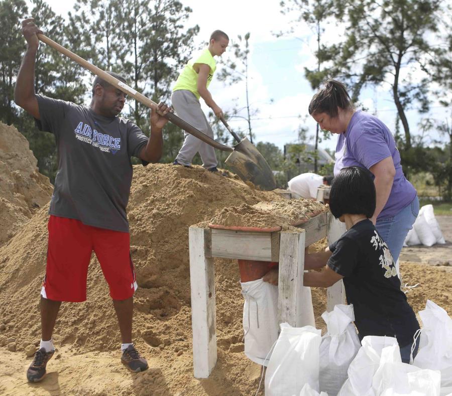 Haskel Johnson, Daniel Tippett, Jennifer Tippett y Nobuko Johnson llenan sacos de arena en Lynn Haven, Florida. (Patti Blake / News Herald vía AP) (semisquare-x3)