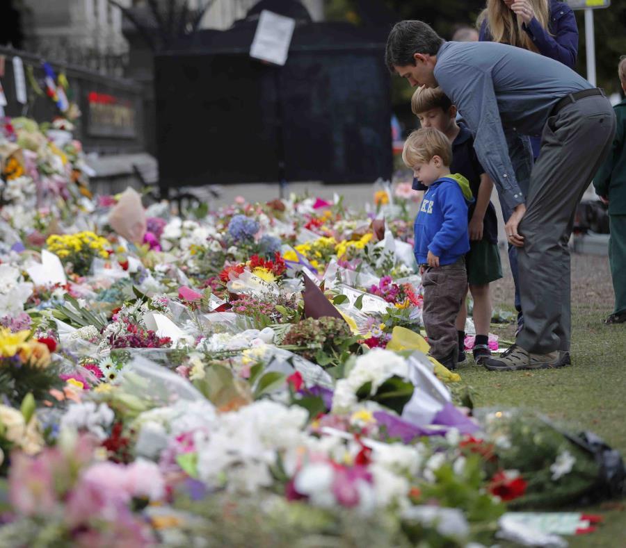 Dolientes colocan flores frente a un muro en los Jardines Botánicos de Christchurch, Nueva Zelanda (semisquare-x3)