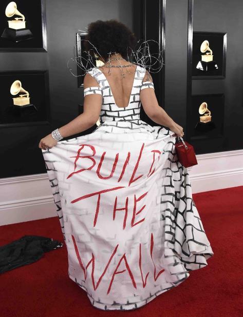 """La cantante Joy Villa, quien está abiertamente identificada con el Partido Republicano, lució un vestido que inicialmente parecía una cortina de hierro, pero que al abrirlo revelaba una muralla de ladrillos con el mensaje """"Build The Wall"""". (AP) (vertical-x1)"""