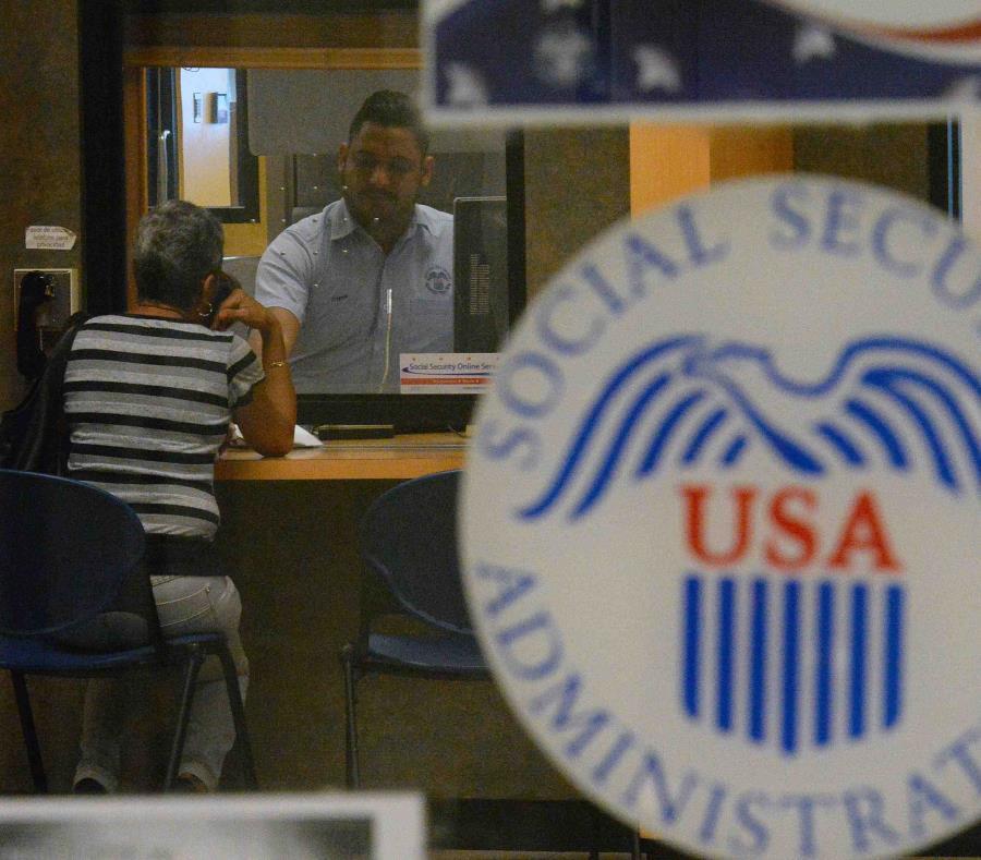Un empleado del Seguro Social atiende a una mujer en las oficinas de la agencia federal en San Juan. (GFR Media) (semisquare-x3)