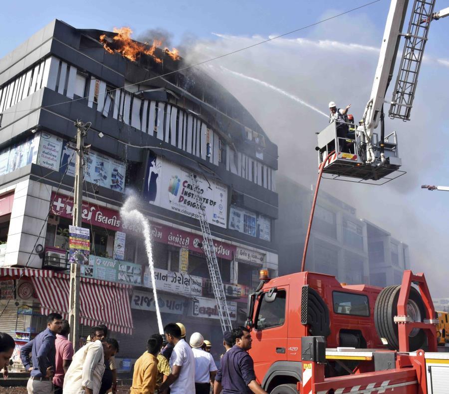Los bomberos combaten las llamas en un edificio en Surat, en el estado de Gujarat, India, el viernes 24 de mayo de 2019. (AP / Sarju Parekh) (semisquare-x3)