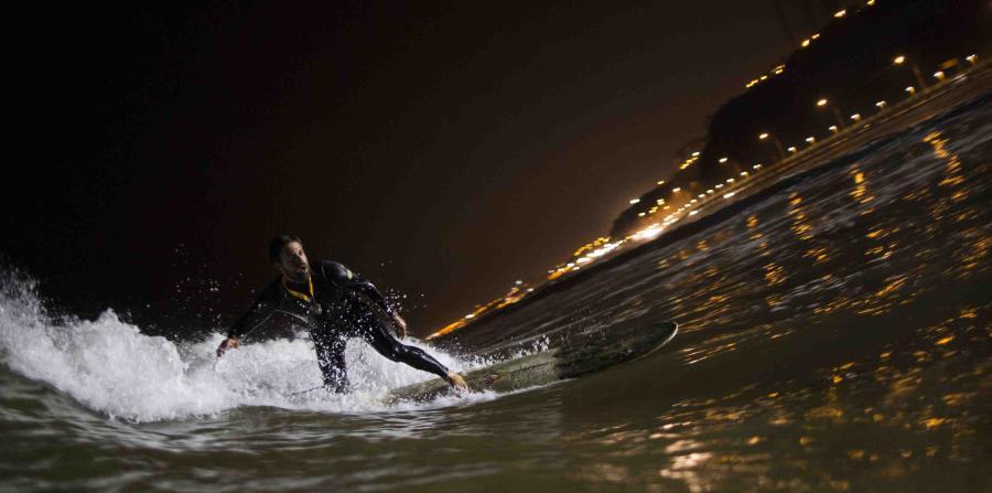 Ernesto Benavides monta una ola en las aguas de la playa de La Pampilla en Lima, Perú. (horizontal-x3)