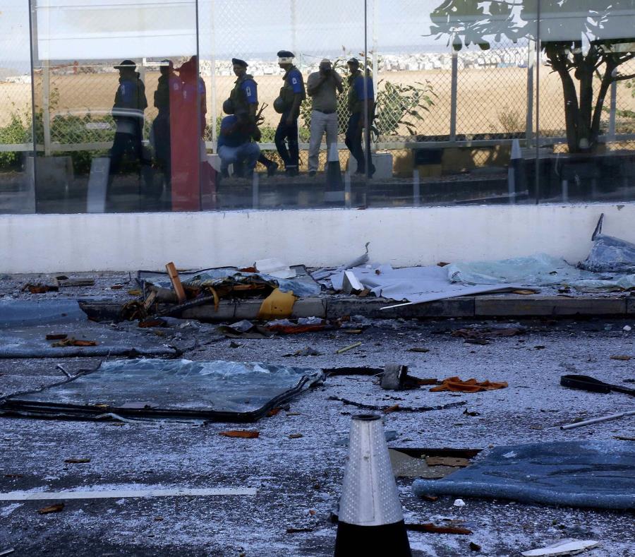 Miembros de las Fuerzas de Seguridad se reflejan en la fachada del dañado hotel Kingsbury, este lunes (semisquare-x3)