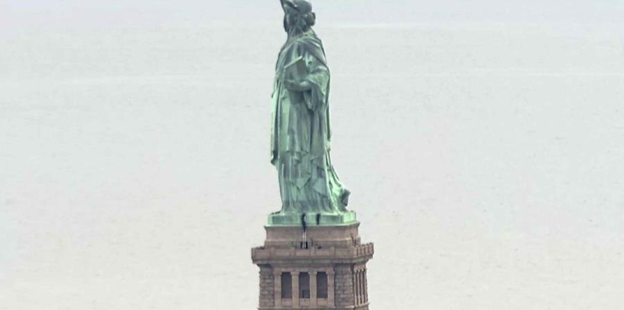 Personas escalando el pedestal de la Estatua de la Libertad. (AP) (horizontal-x3)