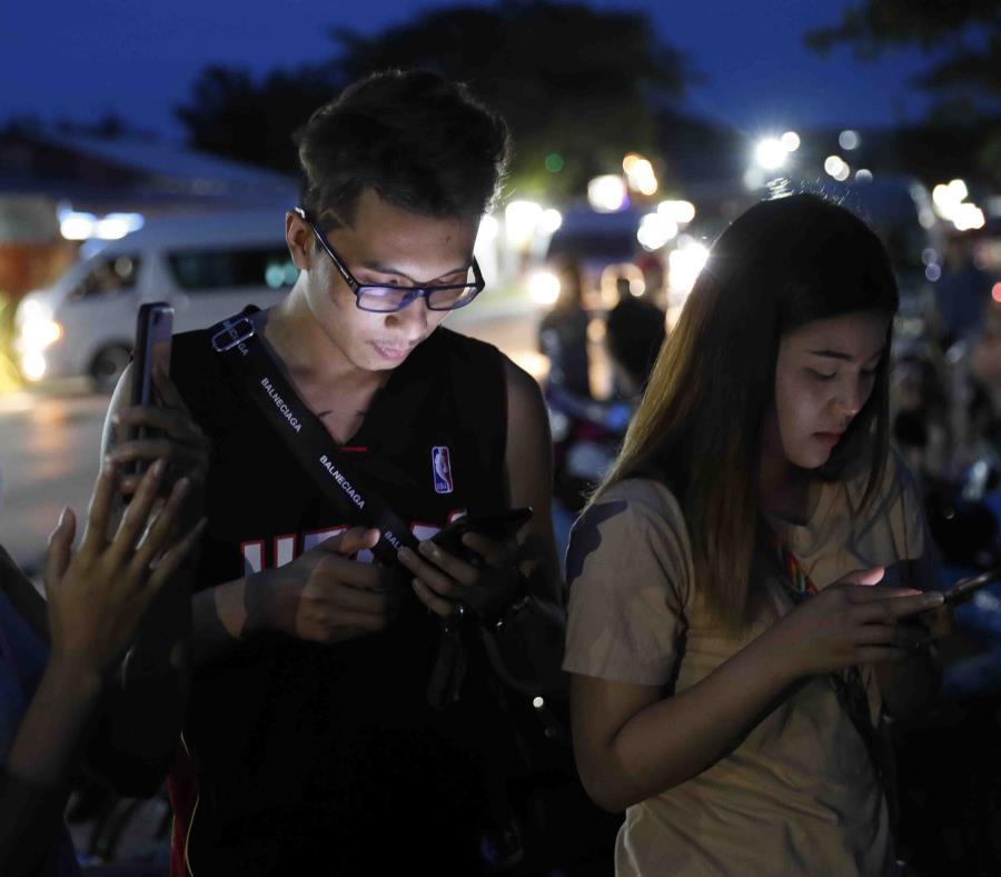 Un grupo de jóvenes observan sus celulares. (AP) (semisquare-x3)