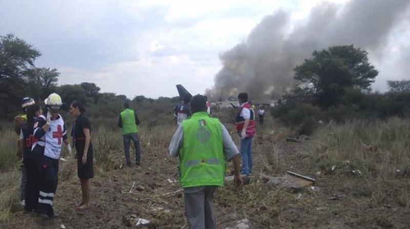 Rescatistas intentan llegar hasta el avión incendiado. (AP) (horizontal-x3)