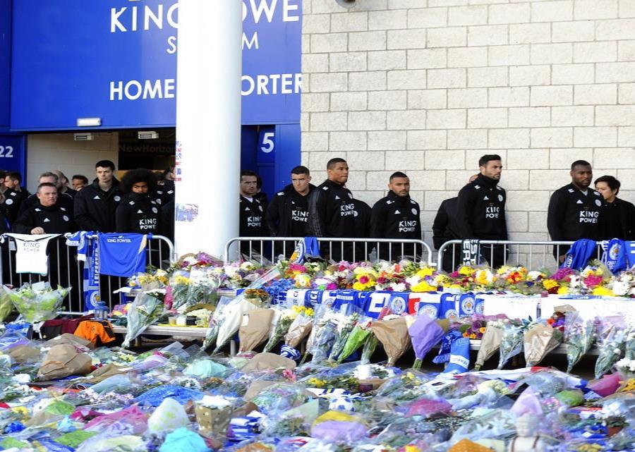 Los jugadores del Leicester City observan los tributos que deja la gente frente al estadio tras el acciedente de un helicóptero en el que murieron el propietario del club Vichai Srivaddhanaprabha y otras cuatro personas. (semisquare-x3)