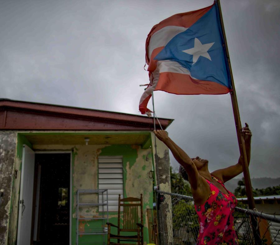 Una mujer frente a su residencia en Yabucoa durante el paso de Beryl por el sur de la isla (semisquare-x3)