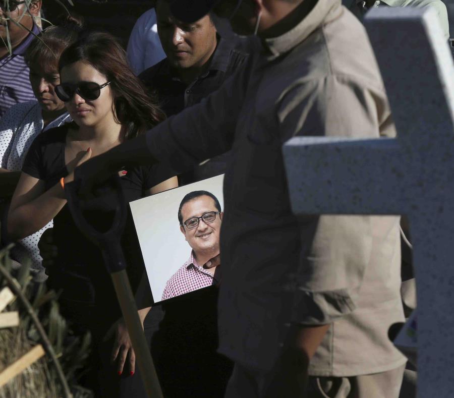 Fotografía de archivo del 31 de mayo de 2018, de un hombre portando un retrato del asesinado periodista Héctor González Antonio mientras su hija, a la izquierda, llora durante su funeral en la Ciudad de México. (AP) (semisquare-x3)