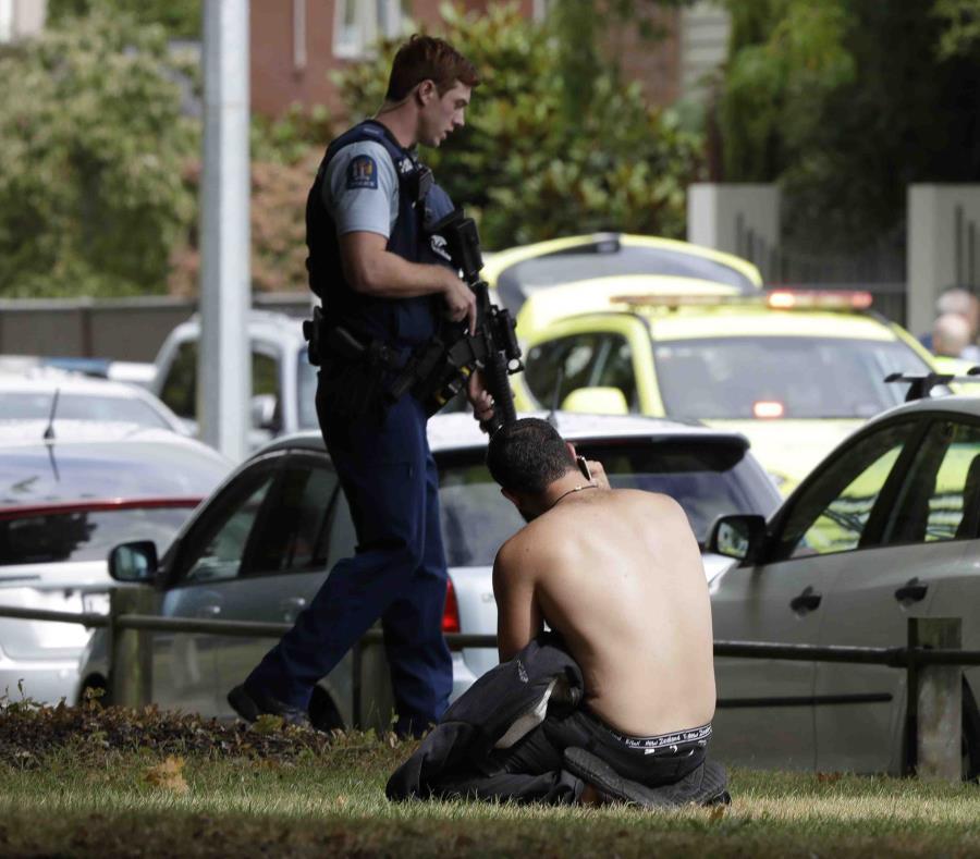 Un hombre descansa en el suelo mientras habla por su teléfono celular del otro lado de la calle de una mezquita en Christchurch, Nueva Zelanda (semisquare-x3)