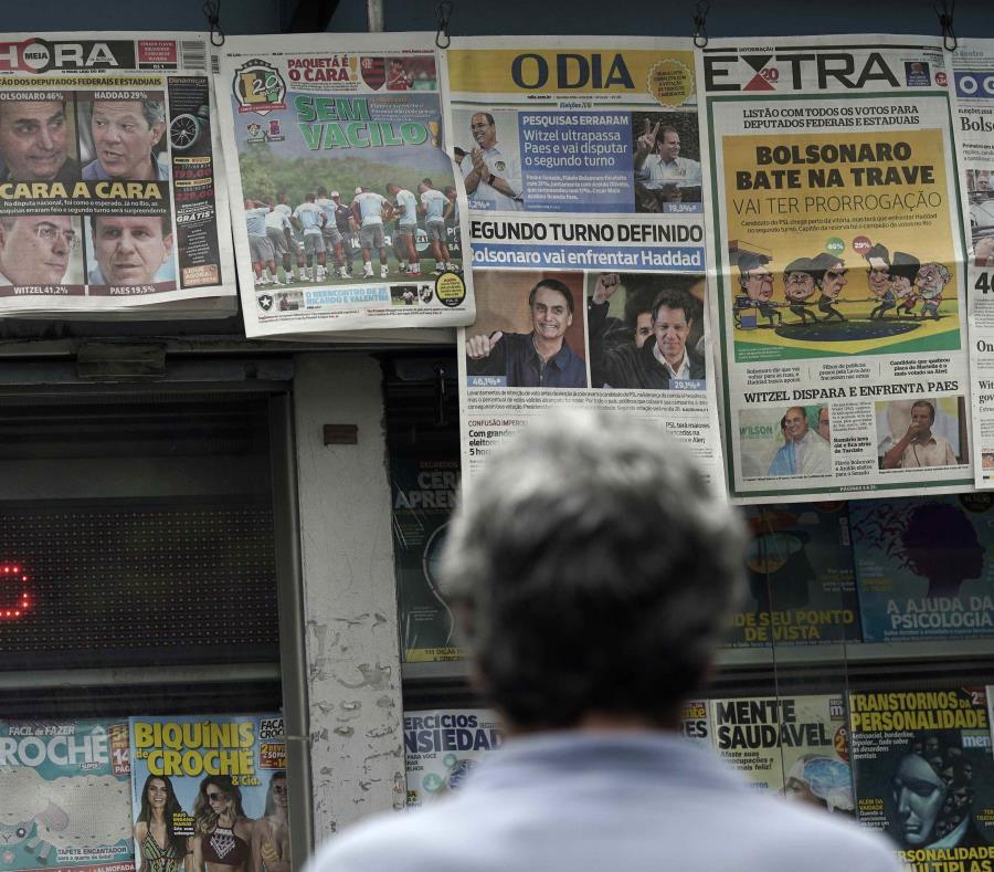 Un hombre lee los encabezados que anuncian los resultados de la elección presidencial de Brasil en Río de Janeiro. (AP / Leo Correa) (semisquare-x3)
