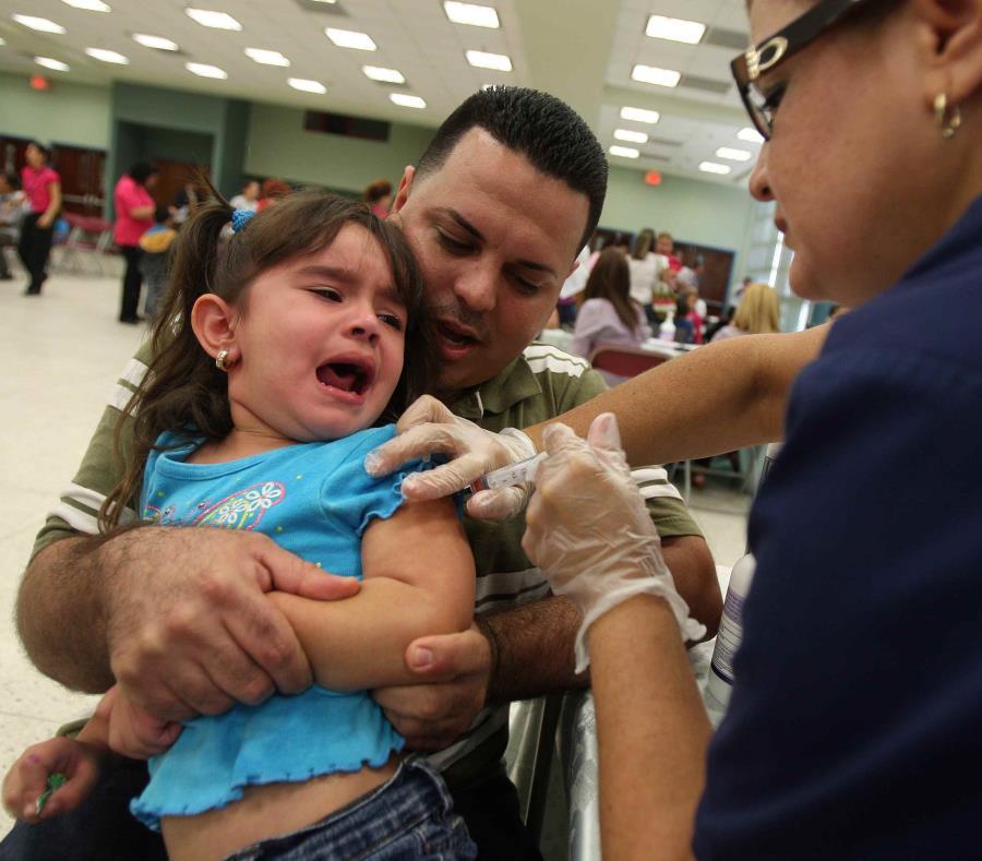 Un padre sujeta a su hija mientras una profesional de la salud la vacuna. (GFR Media) (semisquare-x3)