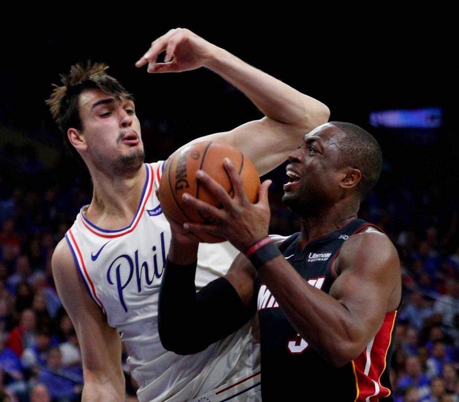 Dwyane Wade del Heat de Miami trata de disparar ante Dario Saric de los 76ers de Filadelfia