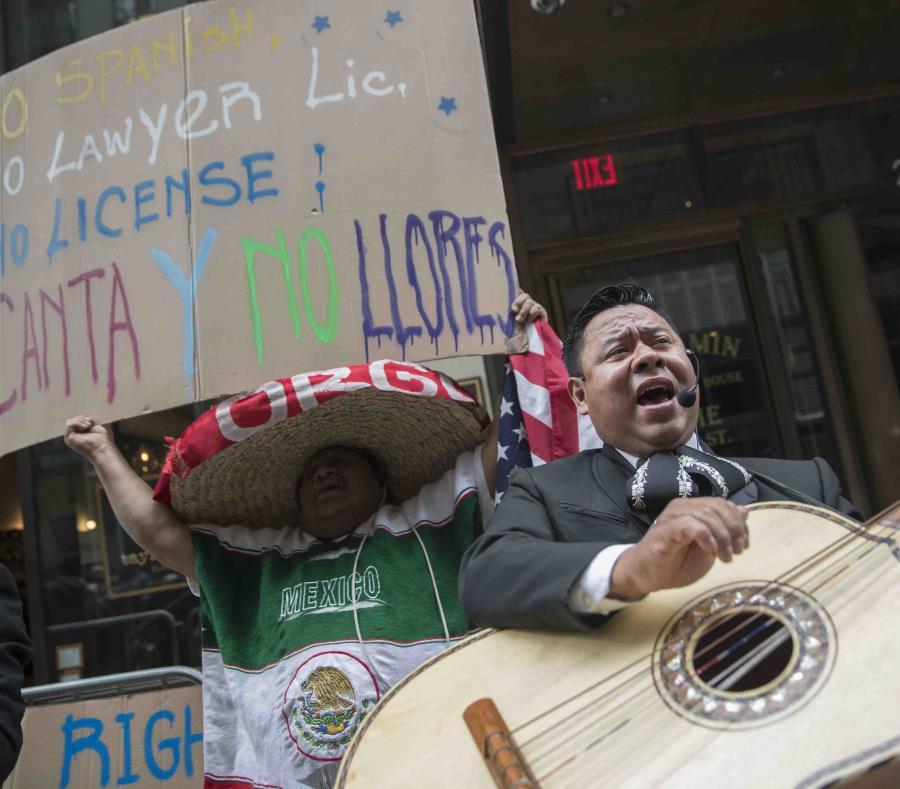 Un manifestante baila y canta con un mariachi durante una protesta al otro lado de la calle donde está el edificio que alguna vez albergó la oficina del abogado Aaron Schlossberg el viernes 18 de mayo de 2018. (AP) (semisquare-x3)