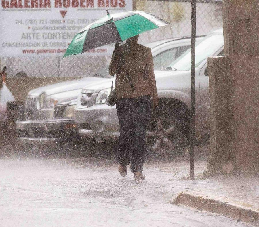 Una mujer camina por una calle con su sombrilla en mano.  (GFR Media) (semisquare-x3)