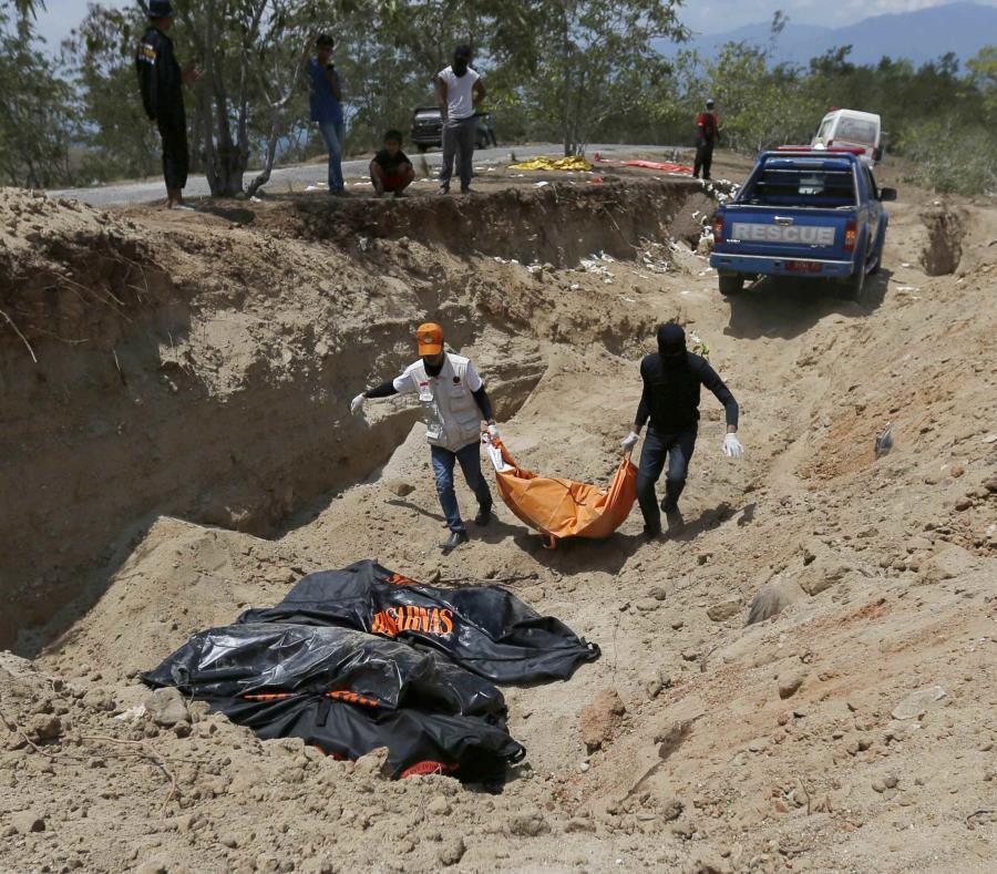 Rescatistas cargan los cadáveres para enterrarlos en una fosa común. (AP) (semisquare-x3)