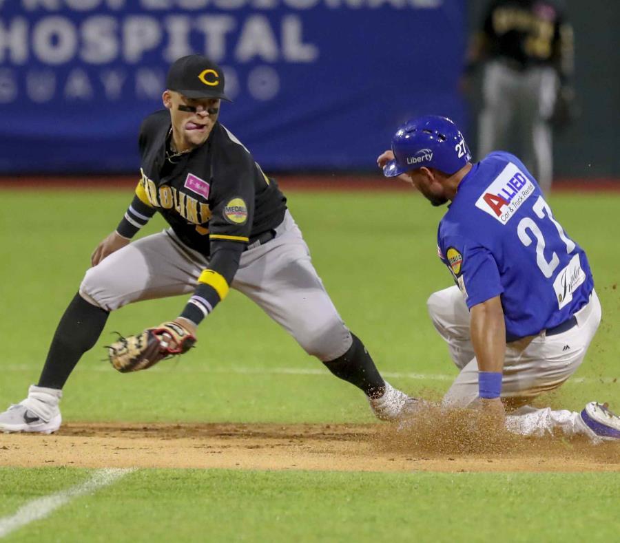 El lanzador de Carolina, Isan Diaz (a la izquierda) y intenta detener al jugador de Santurce, Raymound Fuentes, mientras llega a salvo a la segunda base. (semisquare-x3)