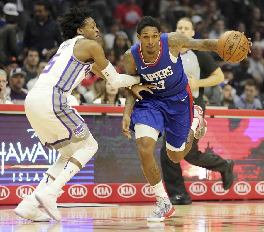 Lou Williams (23), de los Clippers de Los Ángeles, intenta superar la marca de De'Aaron Fox (5), de los Kings de Sacramento, en la primera mitad del encuentro en Los Ángeles. (semisquare-x3)