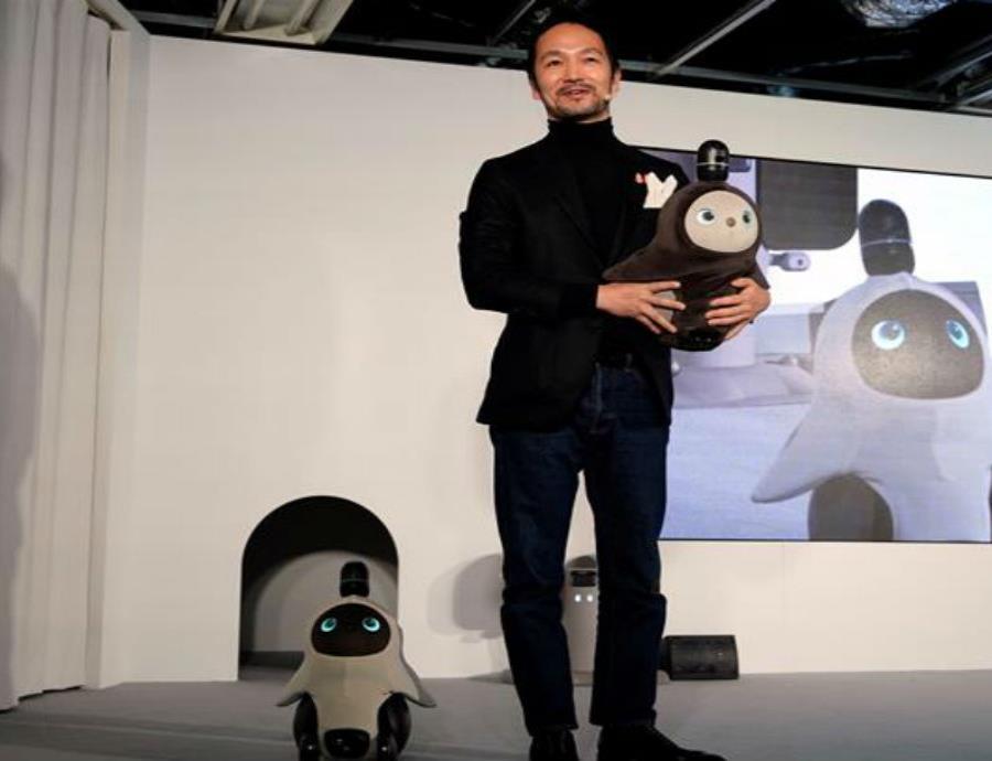 El ingeniero nipón Kamame Hayashi, responsable de la compañía Groove X, posa con sus nuevos robots domésticos
