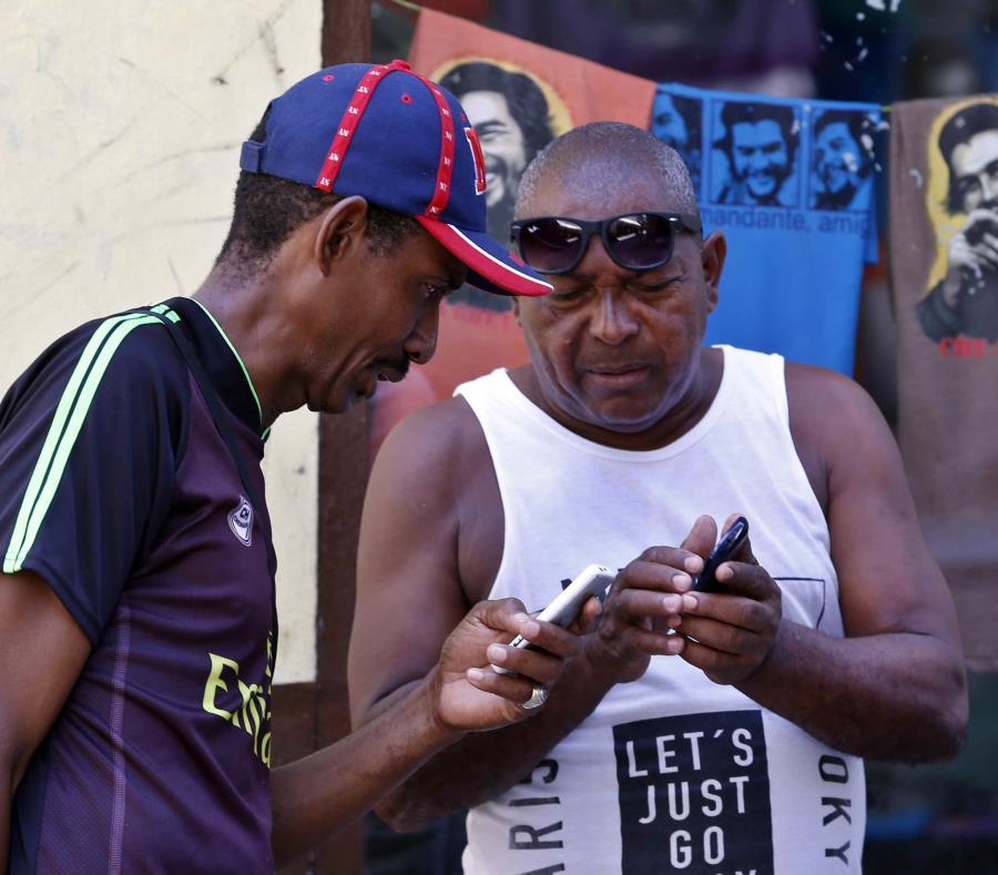 Dos clientes de Etecsa intentan conectarse al Internet mediante sus teléfonos móviles en Cuba. (EFE / Ernesto Mastrascusa) (semisquare-x3)