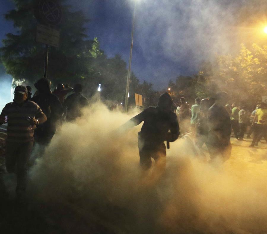 Manifestantes pasan por una nube de gas lacrimógeno durante una protesta contra el gobierno en Tirana. (AP/Hektor Pustina) (semisquare-x3)
