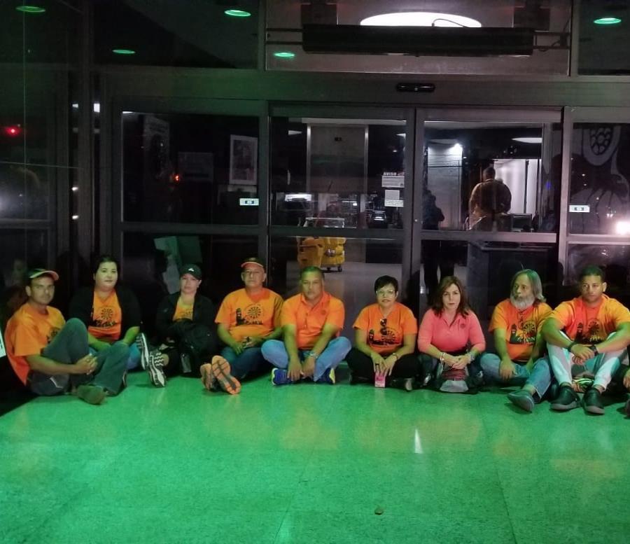Los empleados unionados permanecen sentados frente a la entrada principal de la sede de la agencia (semisquare-x3)