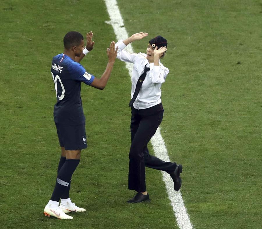 Una mujer que irrumpió en la cancha se acerca al delantero francés Kylian Mbappé durante la final del Mundial en el estadio Luzhniki de Moscú, el domingo 15 de julio de 2018. (AP) (semisquare-x3)
