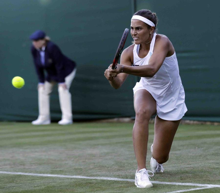 Mónica Puig le devuelve la pelota a Julia Goerges durante el partido de hoy en Londres. (AP / Ben Curtis) (semisquare-x3)