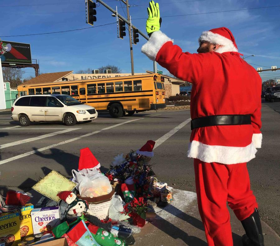 En esta fotografía del 18 de diciembre de 2018, Jimmy Izbinski, vestido con un traje de Santa, saluda a los automovilistas que pasan por una marihuana navideña en Toledo, Ohio. (AP) (semisquare-x3)
