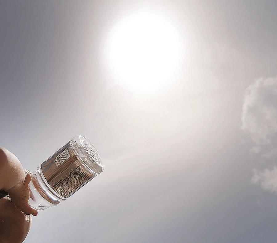 Un hombre bebe agua para aliviar el calor del día. (semisquare-x3)