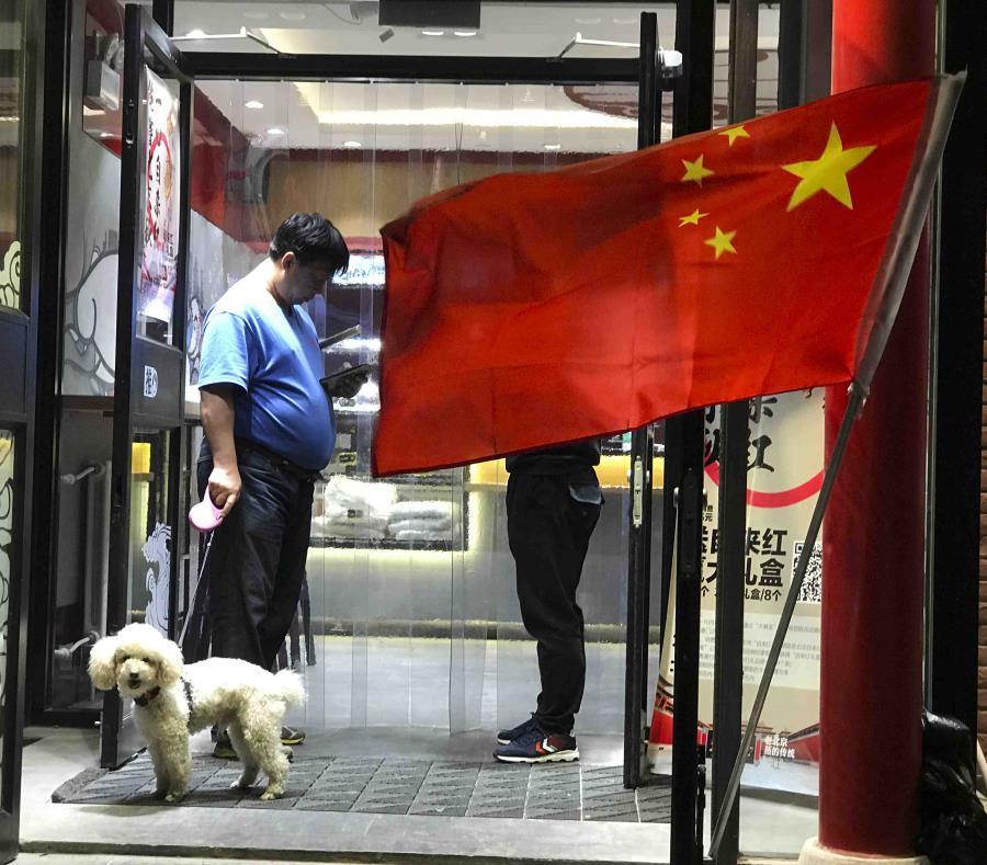 En esta imagen de archivo, tomada el 3 de octubre de 2017, un hombre pase a su parro a la salida de un restaurante ante el que ondea una bandera china, en Beijing, China (semisquare-x3)