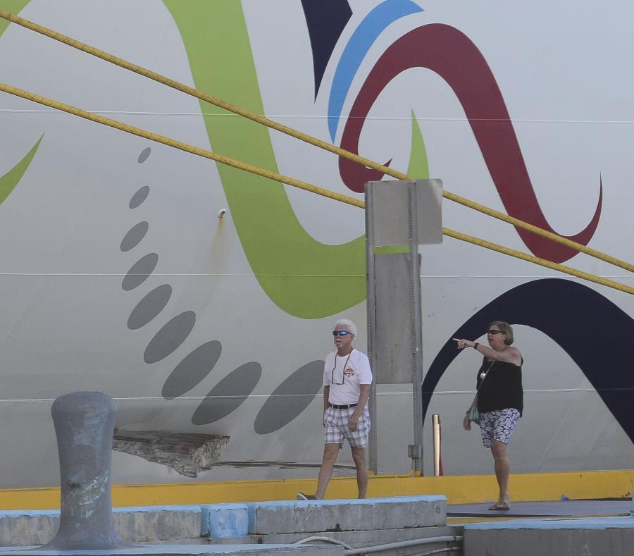 Unos turistas caminan frente al golpe que recibió el crucero. (semisquare-x3)