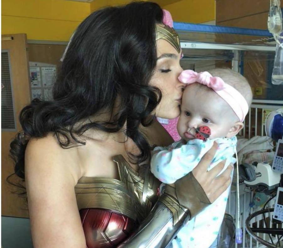 En esta imagen proporcionada por Kelly Swink Sahady la actriz Gal Gadot, vesitda como la Mujer Maravilla, besa a la hija de Sahady, Karalyne, durante una visita al Hospital de Niños Inova en Falls Church, Virginia. (AP) (semisquare-x3)