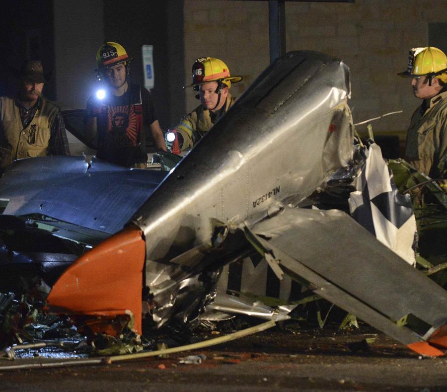 Los bomberos atienden la escena donde atienden el accidente de un avión vintage. (AP) (semisquare-x3)