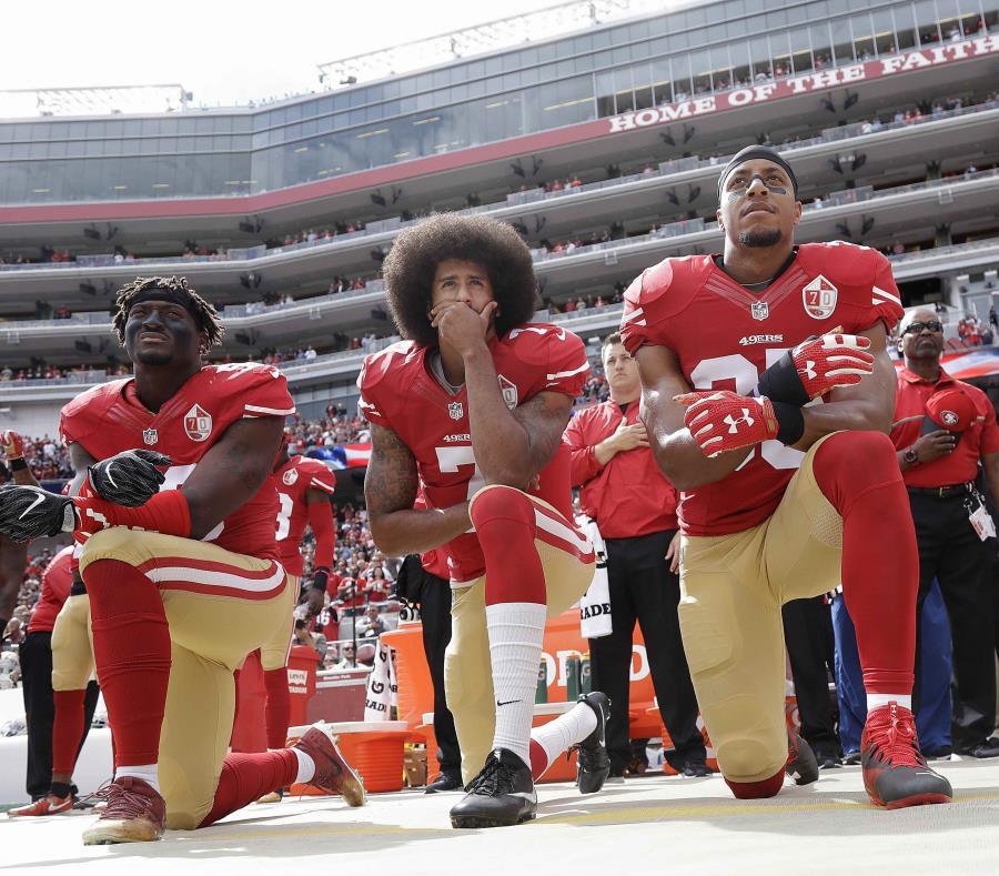 Colin Kaepernick (centro), de los 49ers de San Francisco, se arrodilla con otros compañeros durante la interpretación del himno nacional. (AP) (semisquare-x3)