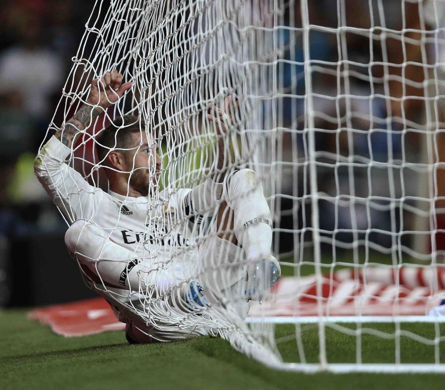 Sergio Ramos, del Real Madrid, parece acostarse en la malla de la portería durante un partido. (AP) (semisquare-x3)
