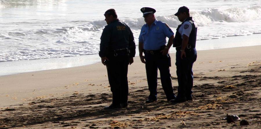 Tres agentes de la Policía investigan un ahogamiento en la playa. (GFR Media) (horizontal-x3)