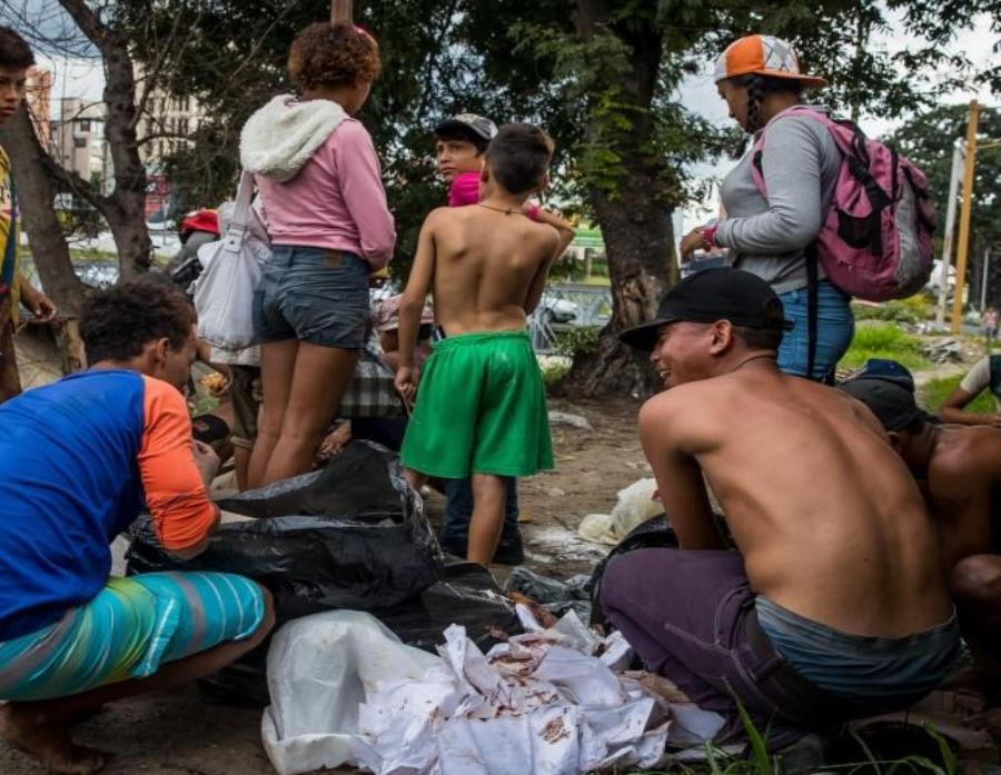 Un grupo de niños busca comida entre las bolsas de basura que obtuvieron en una panadería. (EFE / Miguel Gutiérrez). (semisquare-x3)