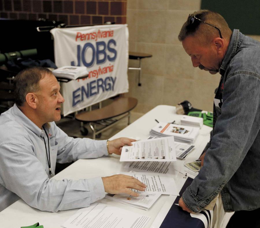 En esta fotografía del jueves 2 de noviembre de 2017, un reclutador de la industria del gas de esquisto, a la izquierda, conversa con una persona que asistió a una feria de empleo en Cheswick, Pensilvania. (AP) (semisquare-x3)