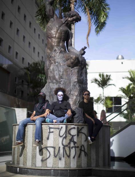 Tres jóvenes están sentados en la base de una estatua que fue escrita con un mensaje de repudio a la Junta. (vertical-x1)