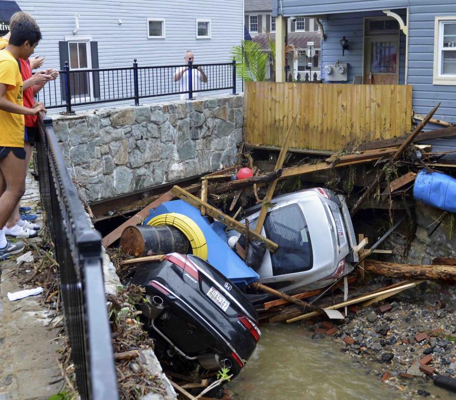 Residentes se reúnen en un puente para observar los daños causados por una inundación que arrasó con Ellicott City, en Maryland. (AP) (semisquare-x3)