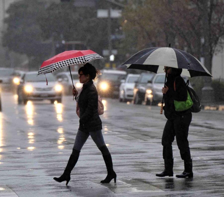 Dos mujeres se cubren con sombrillas de la lluvia, mientras caminan por una carretera. (semisquare-x3)