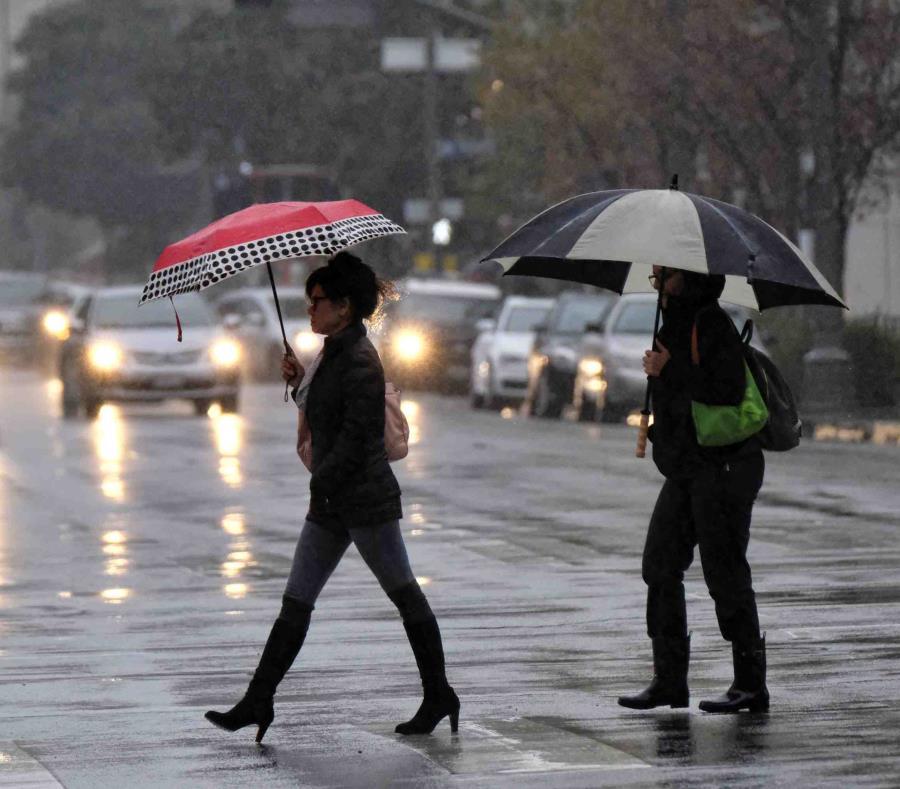 Dos mujeres se cubren con sombrillas de la lluvia, mientras caminan por una carretera. (Archivo / AP) (semisquare-x3)