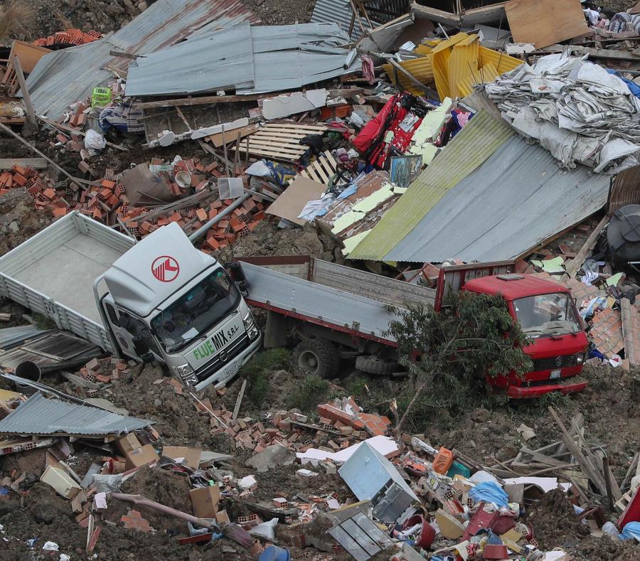 Bomberos buscan sobrevivientes que pudieran estar atrapados en los escombros después de un derrumbe en un barrio de La Paz, Bolivia. (semisquare-x3)