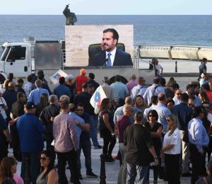 Empleados de agencias se reúnen a las afueras del Capitolio para ver el mensaje de Rosselló