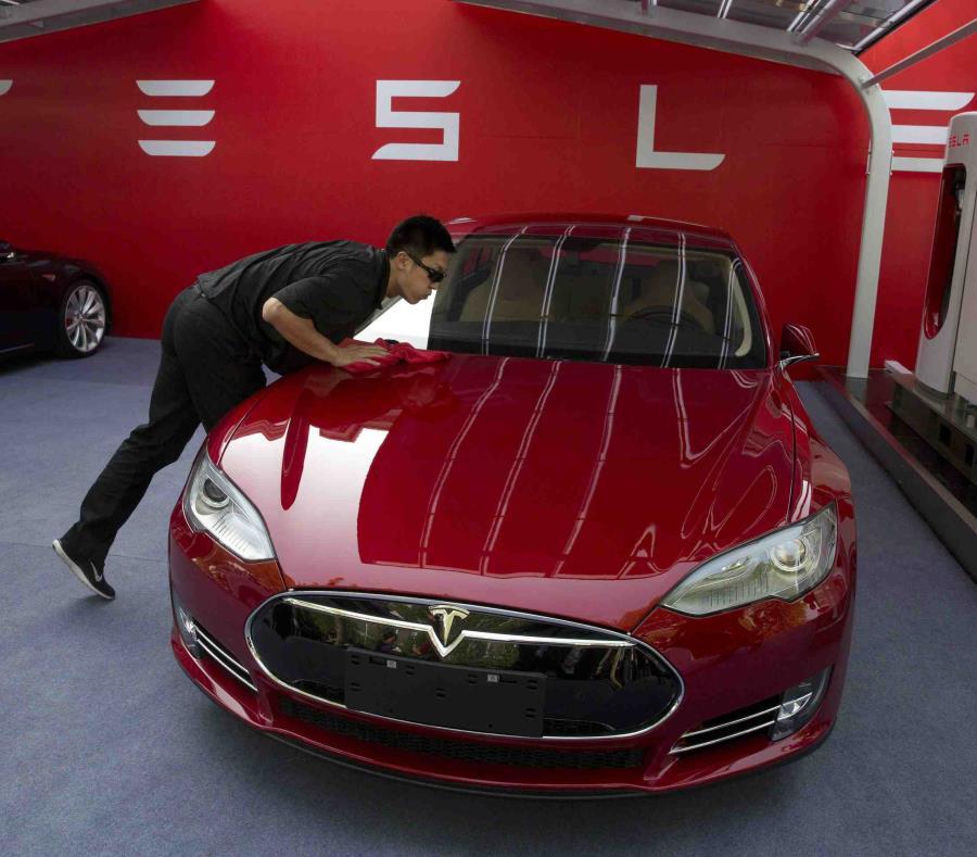 Un trabajador limpiando un sedán Tesla Model S. (semisquare-x3)