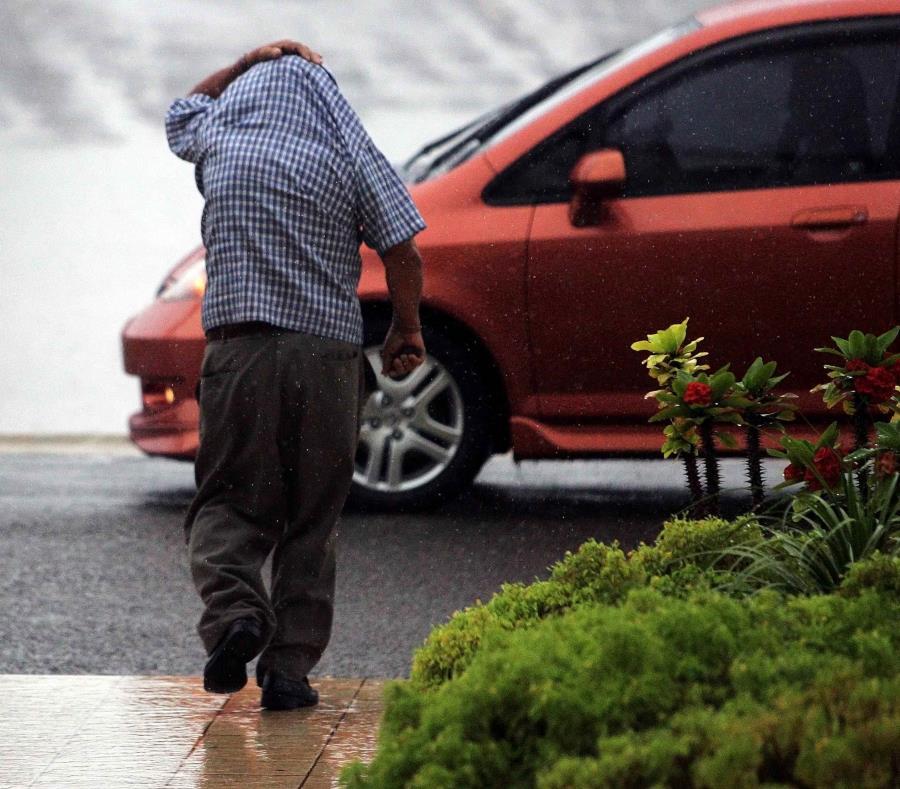 Un hombre se cubre con su camisa para evitar mojarse con la lluvia (semisquare-x3)