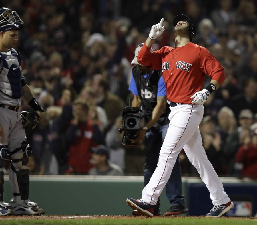 El jugador de los Medias Rojas de Boston, J.D. Martínez, apunta al cielo luego de pegar un jonrón de tres carreras, mientras pasa cerca del receptor de los Yanquis de Nueva York, el dominicano Gary Sánchez (semisquare-x3)