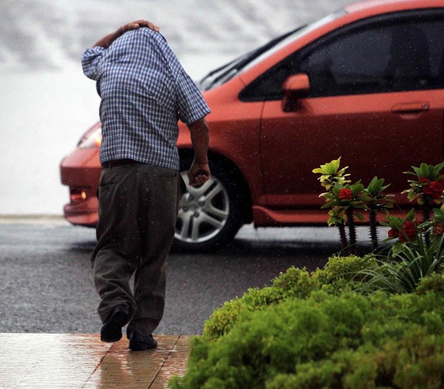 Un hombre se cubre con su camisa de la lluvia. (GFR Media) (semisquare-x3)