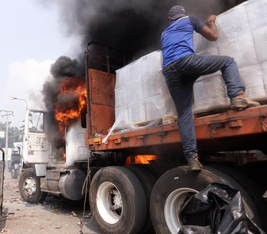 Personas intentan remover parte de la ayuda humanitaria transportado por un camión que fue quemado el pasado 23 de febrero. (EFE / Deibison Torrado) (semisquare-x3)